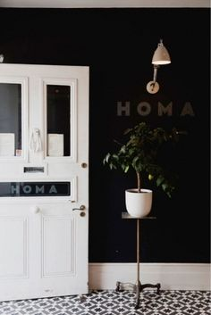 Homa | London. More inspiration for the basement. love the tile, black wall, plant and HOME decal.