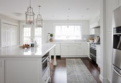 Stunning kitchen features a pair of Hudson Valley Lighting Mansfield Lanterns illuminating a white center island with legs topped with Silestone Bianco River. Kitchen with white shaker cabinets paired with Bianco River countertops and a white and gray iridescent tiled backsplash.