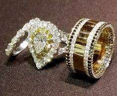 Lady's pear-shaped white diamond ring is embraced by fancy yellow diamonds, surrounded by white diamonds, kissed by V-shaped shank. Matching band features pear-shaped diamonds in shared prong style. Gentleman's band is embraced by white & black diamonds,
