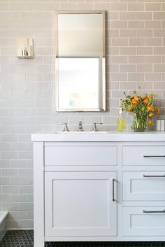 Chic bathroom features a wall clad in gray subway tiles lined with a white dual washstand and a long polished nickel mirror alongside a black tiles floor.