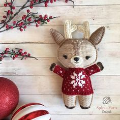 Deer wearing red sweater with baubles and holly