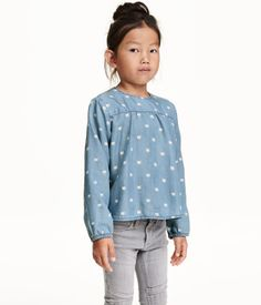 CONSCIOUS. Wide-cut blouse in washed denim made from Tencel® lyocell with a printed pattern. Yoke at front, opening with button at back of neck, and elasticized cuffs. Rounded hem, slightly longer at back.