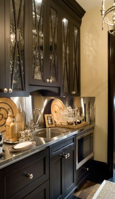Black cabinets with glass doors, stainless steel counter -- Joy Tribout Interior Design