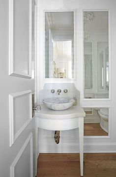 French powder room features a small white washstand with tapered legs fitted with a curved marble countertop topped with a round marble bowl sink situated under a spigot faucet mounted on a curved marble backsplash situated under mirror framed with trim moldings.