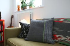 The grey cushion with green stripe was hand woven on a loom by Jamie's mom.