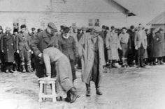 Salaspils, Latvia, A prisoner whipping another prisoner under the supervision of an SS guard.