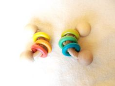 Two hardwood maple curvy rattles with rainbow colored rings. The wooden rings make a beautiful and pleasant rattling sound when baby plays with this toy. The rounded ends are the perfect size for baby to mouth.  Appropriate for ages 6 months to 2 years.  Each piece is hand rubbed with organic homemade beeswax wood polish.  This set includes two rattles with rainbow colored rings  The color of rings is customizable, please let us know if you would like different colors than what is shown…