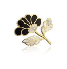 TIFFANY & CO. A Gold, Jade, and Mother-of-Pearl Brooch Designed as a polished gold flower, set with inlaid black jade petals and mother-of pearl leaves, mounted in 18K yellow gold, length 2 inches.