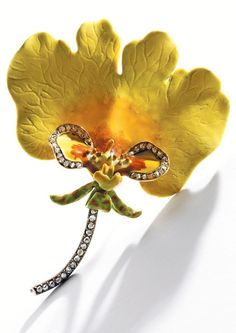 An Antique Gold, Enamel and Diamond Orchid Brooch, Paulding Farnham for Tiffany & Co., circa 1890. Designed as the variety of orchid 'oncidium varicosum rogersii,' the petals decorated in vibrant yellow and faint orange enamel, accented by the lip with yellow, ochre and cream-coloured enamel bordered by rose-cut diamonds, the descending curled sepals of chartreuse and orange-hued enamel supported by a column of rose-cut diamonds, signed Tiffany & Co. #Tiffany #antique #Farnham #brooch