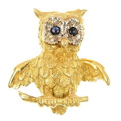 A sapphire and diamond owl brooch. he brooch designed as an owl, with sapphire cabochon and diamond accent eyes, to the detailed carved feather body and feet perched on a textured branch