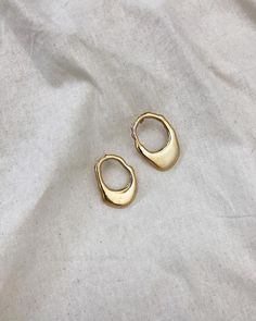 Minimalist style jewellry gold earrings on white linen.