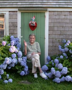 Kurt Vonnegut surrounded by hydrangeas. And a garden gnome. On a pig.
