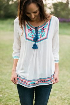 Ivory lightweight top with colorful embroidery details and a tie at the  neck.   Model is 5'10'' wearing size Small