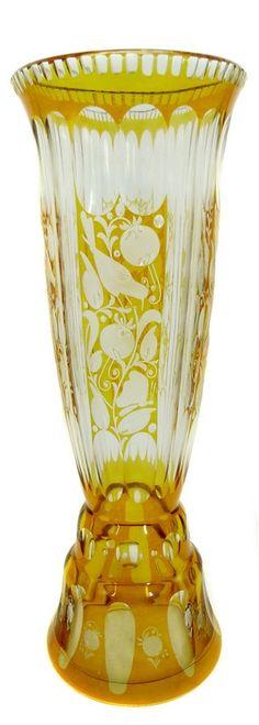 Hohe Vase aus farblosem Glas mit Silbergelbbeize, getreppter, konkaver, zylindrischer Korpus, Wandung ornamental durchschliffen mit teils geblänkter Gravur: Vogel-, Blatt- und Blütenstilisation, verwärmter Vasenrand mit Zierschliffdekor, polierte Standfläche mit Schiebespuren. Vase befindet sich im heilen Zustand im Inneren mit leichten Kalkablagerungen. Glasfachschule Haida um 1915, Vertrieb Joh. Oertel & Co., Haida. Höhe: ca. 25,8 cm.