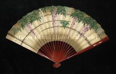 Fan  1905  Folding fan. Printed and hand-painted paper leaf with design of wisteria in white, purple and green. The reverse side of the leaf has a speckled background with hand-painted crossed American and Japanese flags, and a printed menu and musical program, dated July 26, 1905. Lacquered bamboo sticks. (Staten Island Historical Society Collection)