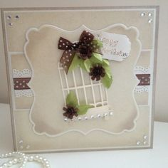 A distressed Centura pearl Layered card with a beautiful cage and floral enhancements.