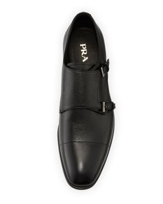 Prada saffiano leather shoe. Double-monk strap across front. Cap toe. Leather lining and insole. Stacked flat heel with metal logo insert. Rubber outsole. Made in Italy.