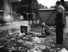 """Moyra Peralta in Spitalfields.  The bonfire corner at Spitalfields Market, 1973. """"There had been deaths here from market lorries reversing. Ted McV., however, died of malnutrition and exposure. """""""