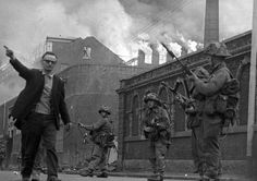 As buildings burn, British Army troops patrol the streets after being deployed to end the Battle of the Bogside in Derry. August 15th, 1969