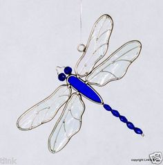 A delightful stained glass blue dragonfly suncatcher. An exclusive design by Link's Stained Glass. Made with blue glass beads for eyes and tail. Iridescent clear textured wings with wire overlay. Dragonfly Stained Glass, Beaded Dragonfly, Stained Glass Suncatchers, Stained Glass Crafts, Glass Butterfly, Faux Stained Glass, Stained Glass Patterns, Stained Glass Windows, Mosaic Glass