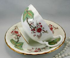Lovely Aynsley Teacup & Saucer, Oban Shape, Gold trimmed, Fine Bone English China made in 1950s. In good condition, no chips, cracks, crazing or repairs. The Saucer measures-5.5 (14cm) in diameter. The Cup opening-3.5 (9cm), with the handle-4.5 (11.5cm) The Height-2.3 (6cm)