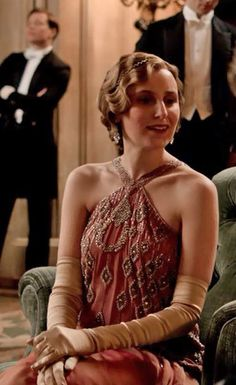 Edith looks very glamorous in a coral beaded halter dress - Downton House Party Season IV