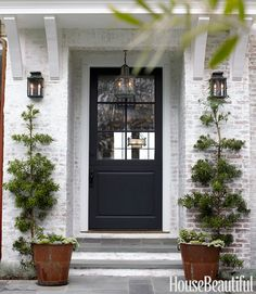 could I DIY this? whitewash the brick at front of the house - love this image. Entrance to a white washed brick house with rusty metal planters on either side, whitewashed stone stairs, a black front door, and lantern style lights Exterior Colors, Exterior Paint, Exterior Design, Stone Exterior, Exterior Homes, Brick Design, Black Front Doors, Front Door Colors, Br House