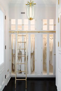 A Fontana Arte vintage light pendant illumiantes a well appointed custom white closet boasting a gold ladder fitted to a gold rail mounted to lighted glass front wardrobe cabinets boasting stacked gold clothing rails. Wardrobe Room, Wardrobe Cabinets, Glass Wardrobe, Walk In Wardrobe, Capsule Wardrobe, Walk In Closet Design, Closet Designs, Wardrobe Design, Master Closet
