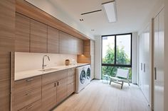 9 Inspirational Laundry Rooms You Need In Your Life // This laundry room has lots of natural light, a wall full of wooden cabinetry, and on the opposite wall, tall wardrobes create additional storage. Modern Laundry Rooms, Large Laundry Rooms, Farmhouse Laundry Room, Laundry Room Storage, Laundry In Bathroom, Modern Room, Light Hardwood Floors, Laundry Room Inspiration, House Ideas