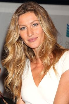 Gisele's curly highlighted hair and natural make up set off with diamond earrings
