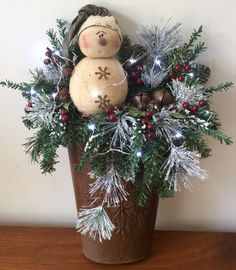 """#8271601~ New for 2016, is a metal wall basket with pierced, laser cut snowflake design. Filled with a vintage snowman, a variety of pines, faux branches, frosted Ming, lacquered branches, glittery leaves, rusty jingle bells and a battery operated, miniature light string. ( Please note: this piece is unable to stand on its own as the container was created with a metal hanging loop suitable for hanging on a wall or door) Measure 19""""H x 13""""W x 6""""D. $38"""