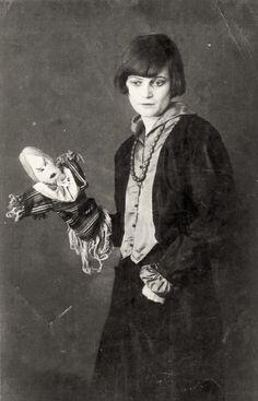 Emmy Hennings with one of her Dada dolls, Zurich, 1917. (1885 - 1948) était une artiste allemande du mouvement dada, danseuse, poétesse et écrivain. Dès 1913, elle fut la compagne puis l'épouse de Hugo Ball, célèbre artiste dadaïste. Elle participa en 1915 à la fondation du Cabaret Voltaire à Zurich qui fut le berceau du dadaïsme. Elle en anima les soirées par ses danses, ses chants et ses poésies. Plus tard, elle assura la subsistance de son couple en travaillant à l'usine.