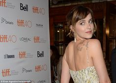 Looking back: The 25-year-old's bird tattoos were visible under the gown's thin straps...