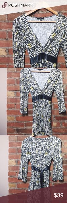 Express Printed V-Neck Dress with Tie Express Printed V-Neck Dress with Tie at Waist. Dark gray and yellow zebra pattern on cream background. Cross-body V-Neck detail accentuated by dark grey satin tie at waist. Three-quarter length sleeve, midi length. Only worn several times, excellent used condition. Express Dresses Long Sleeve