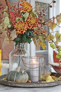 Centerpiece: galvanized tray, white candle, vase of fall leaves + mums, and pumpkins.
