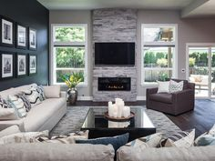 Big open windows lets in tons of natural light in a gray, modern living room. A black accent wall with black-and-white photographs make a bold statement. Neutral furniture keeps the space feeling light and fresh.