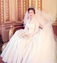 Princess Margaret's wedding dress was designed by Norman Hartnell, the favoured couturier of the royals and was made from silk organza, and a skirt made from some 33 yards of fabric.  Hartnell specifically kept the adornments of the dress such as the crystal embellishments & beading to a minimum in order to suit Margaret's petite frame She was a beautiful bride! The dress now belongs to the British Royal Collection and is part of a display of royal wedding dresses at Kensington Palace in…
