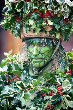 UK - London - A performer (Mummer) dressed as the Holly Man - the winter guise of the Green Man - processes along the Thames in a traditional 'wassail' ...