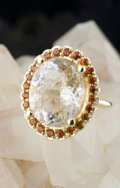 This rutilated quartz ring was designed for a client who loves big and bold jewelry and warm color. We created a halo of burnt orange sapphire surrounding the quartz for extra pop. The entire design is set in 14k yellow gold for an overall warm and glowy effect. A matching tiara band adds even more to this extra bold look. This Rutilated Quartz Ring was commissioned by and named for an Abby Sparks Jewelry client. #uniqueengagementring #orangesapphire #sapphirehalo #denverjewelry…