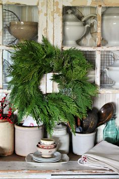 christmas wreath with distressed wood cabinet and pottery.