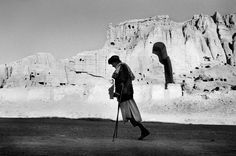 Seamus Murphy, A Hazara victom of the war passes the rock face that once housed the Buddhas of Bamiyan. Bamiyan, June 2003