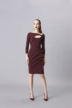 Stretch jersey knee length dress. Plain, asymmetric neckline with cut-out detail, faux wrap skirt with ruching detail, long sleeves. Raw edge hem...