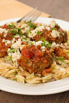Greek Meatballs with Orzo and Feta: Served over orzo and topped with crumbled feta cheese, these meatballs are flavored with Greek-style ingredients, baked, then simmered in tomato sauce until tender.