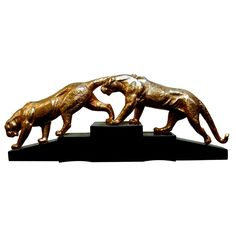 A pair of female lions cast in doré bronze walking on an Art Deco black marble base. This is a very elegant sculpture.