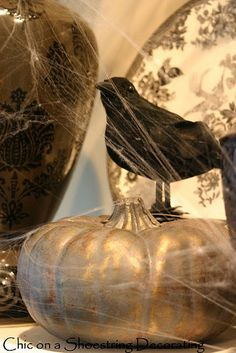 Dollar Tree crows, metallic painted carvable pumpkins, and spider webs for inexpensive Halloween decor