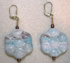 Handcrafted by Teal Palmetto, LLC. These earrings are crafted from large ceramic flower beads in the colors of cream, teal, and brown. Copper accent beads and gold leverback ear wires complete the look. Price: $15.
