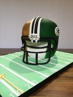 Football Helmet Cake for a football themed birthday. One half is a New Orleans Saints helmet cake, the other half is a Green Bay Packers helmet cake.