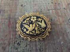 Lovely vintage damascene brooch with an engraved flower, bird and butterfly. Measure just 2 X 1.5 inches with a study trombone clap. In great