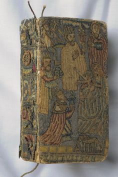 Bible's front and back covers are embroidered with a nativity scene in silk and silver thread on linen