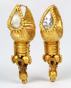 * A large pair of Eastern Roman Gold Earrings, ca. 3rd century BC | The hollow crescent bodies of this pair of large Eastern Roman boat-shaped earrings terminate in wire hoops and are decorated on the front with applied drop-shaped box settings inlaid using glass.  Attached below the earrings is a cluster of ornate sprees and smaller drop-shaped compartments bearing pieces of polished carnelian that echo the larger glass setting above.